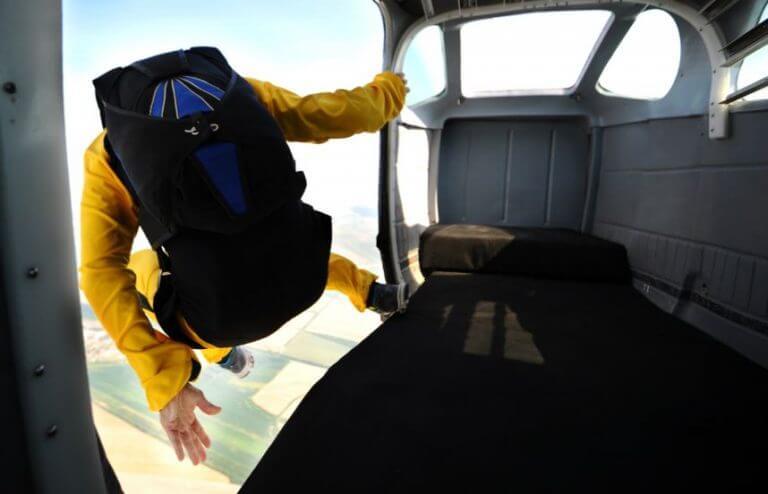 Homem saltando do avião fazendo paraquedismo