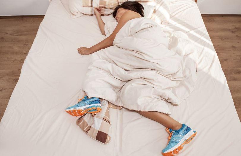 Mulher dormindo com tênis de corrida