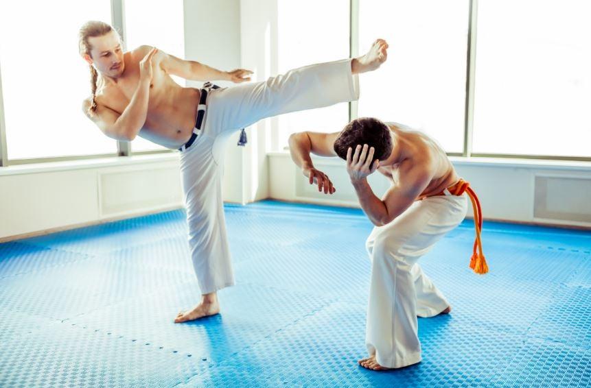 Dos homens dançando capoeira na academia