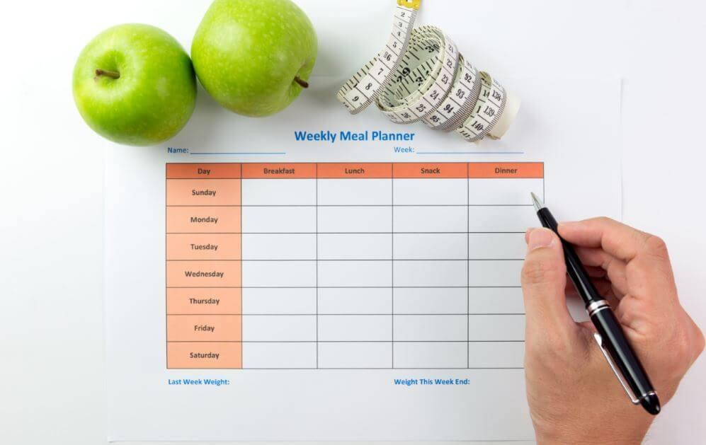 Nutricionista com um calendário, maças e uma fita métrica