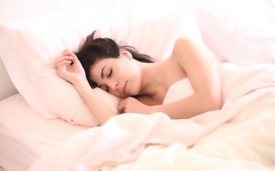 Mulher dormindo em uma cama aconchegante