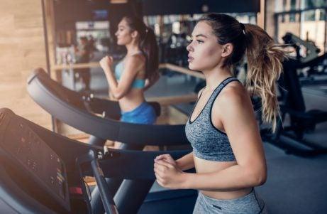 mulheres correndo na esteira na academia