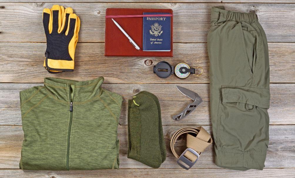 Objetos essenciais para trekking como casaco, canivete e documento.