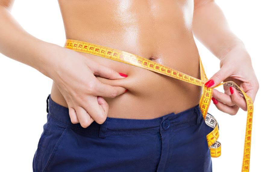 mulher medindo a barriga com uma fita métrica