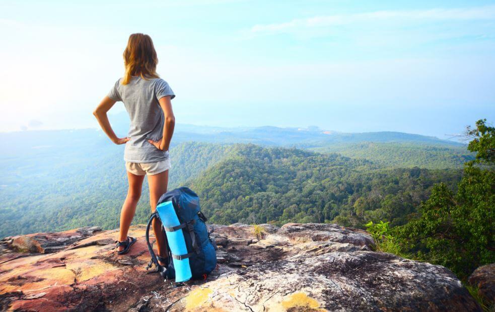 Menina com uma mochila fazendo trekking no topo da montanha