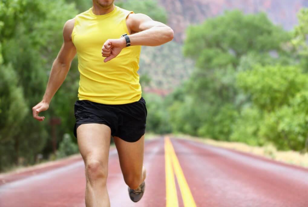Homem  correndo e controlando o ritmo no relógio
