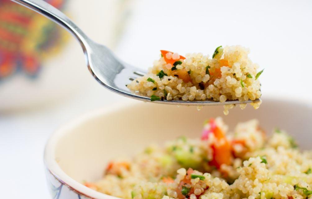 Um garfo com quinoa e um prato de salada