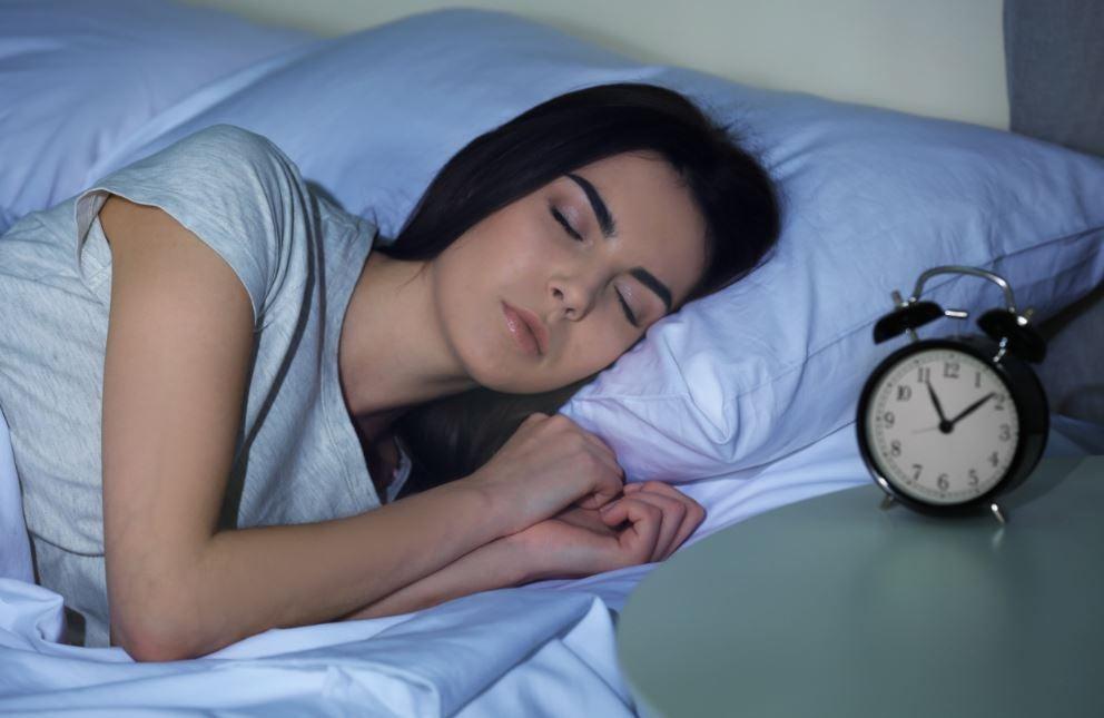 Garota dormindo com despertador do lado