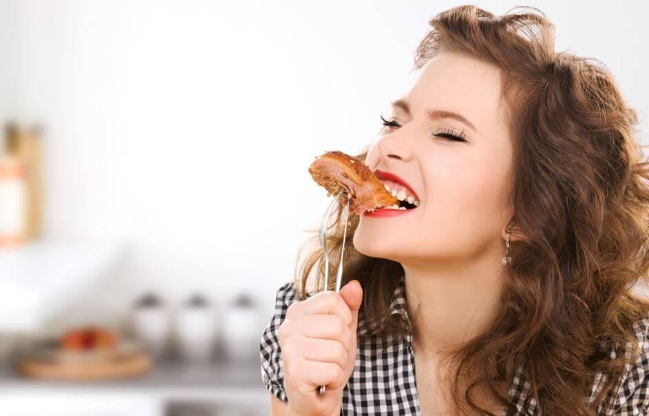 Menina mordendo pedaço de bife