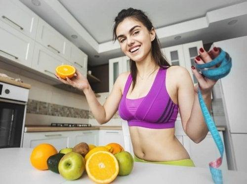 Mulher com roupa de academia, frutas e uma fita métrica na mão.