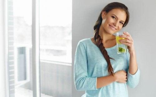 Mulher tomando um copo de água ao acordar