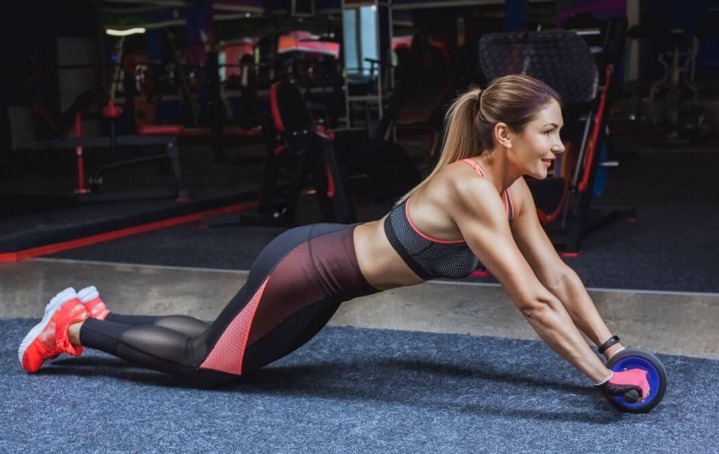 Mulher fazendo abdominal com o rolo