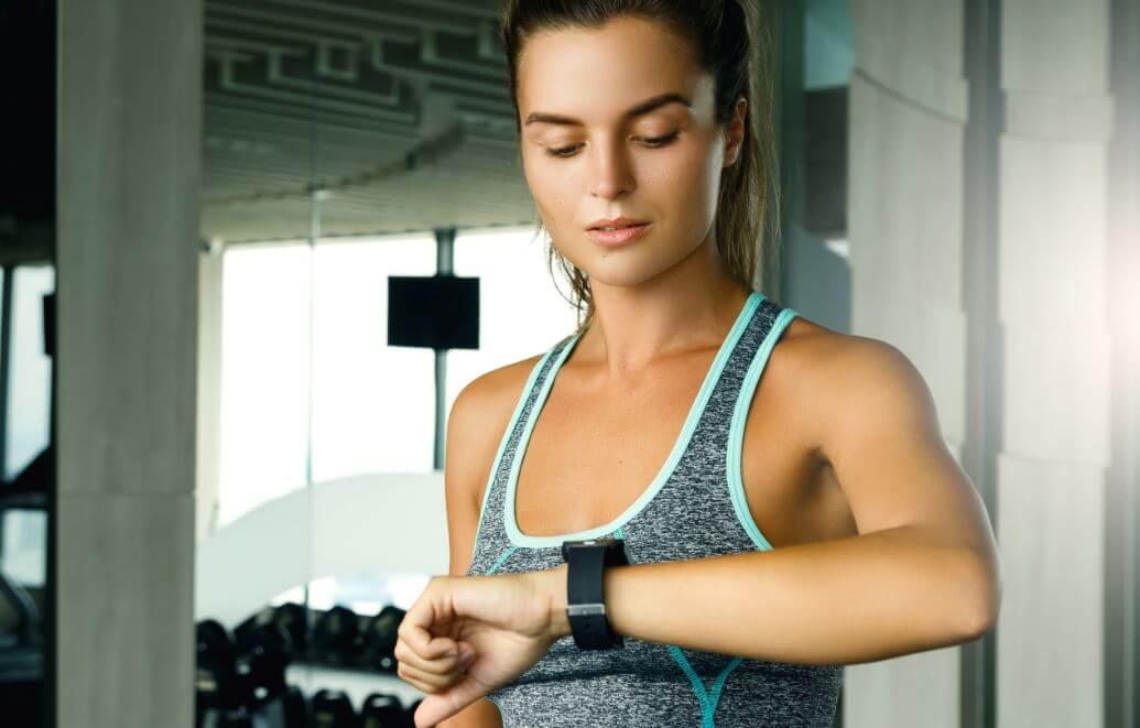 Menina olhando no relógio o tempo de descanso do exercício
