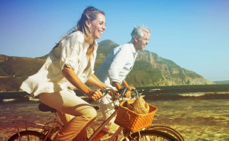 Casal idoso andando de bicicleta na praia