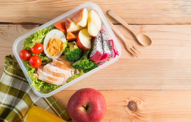 Uma marmita com frango e salada com vegetais e frutas