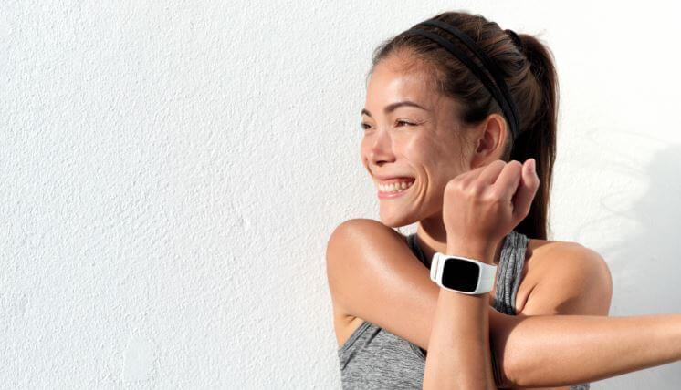 Mulher se alongando com um smartwatch no pulso