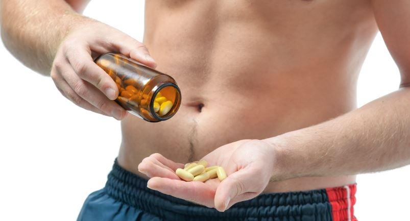 Homem sarado consumindo comprimidos