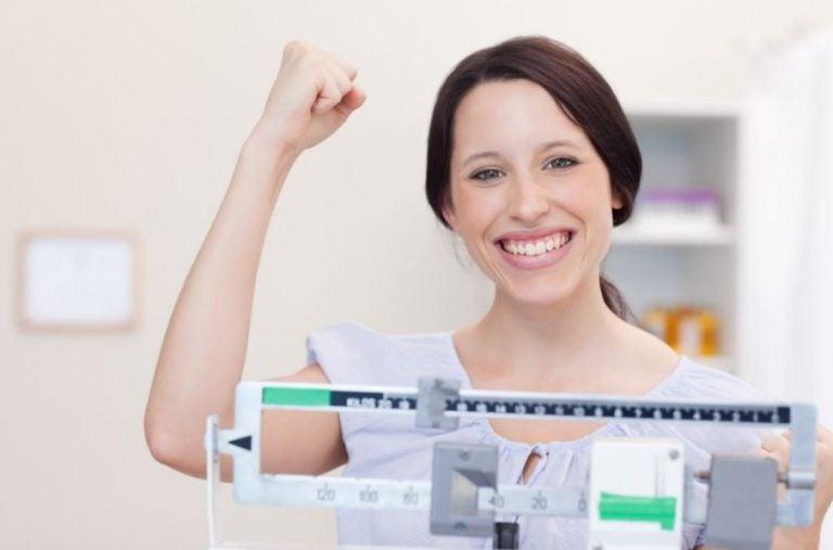 Mulher feliz que perdeu peso se pesando na balança