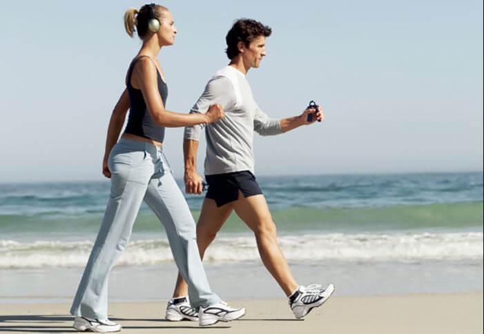 Homem e mulher caminhando na praia