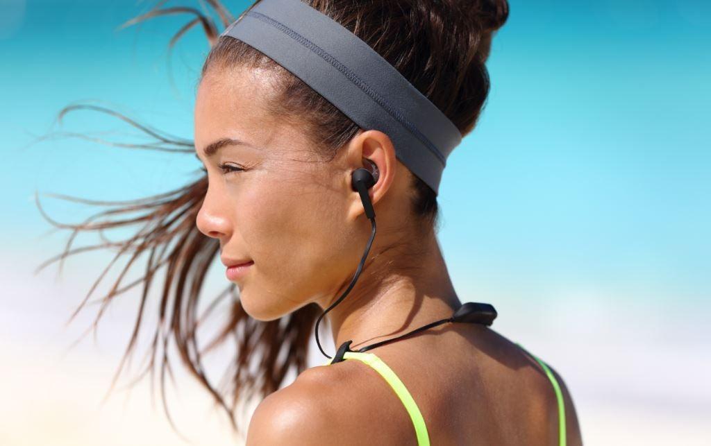 Mulher ouvindo música com fone na praia