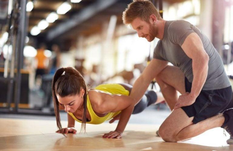 Personal trainer com uma aluna na academia