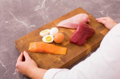 Salmão, frango, ovos e bife em uma tábua de madeira
