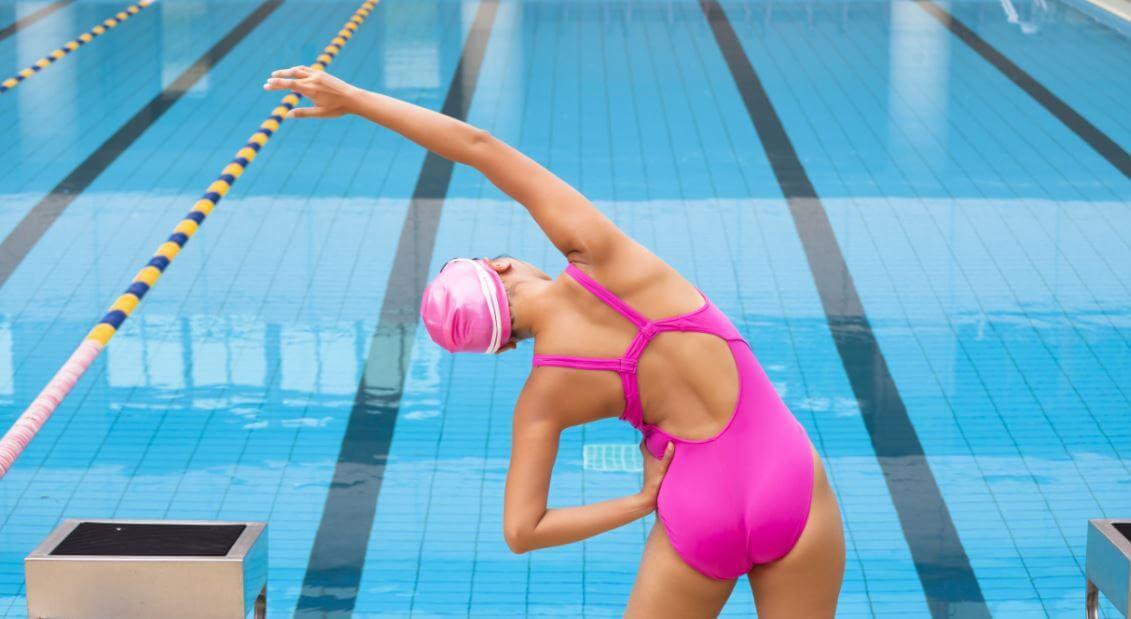 Mulher se alongando antes de entrar na piscina para praticar natação