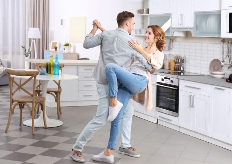 Casal dançando na cozinha de casa