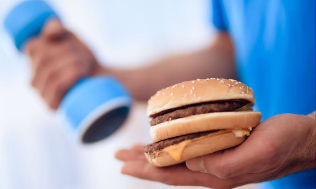 Homem com um peso em uma mão e um hamburguer em outra