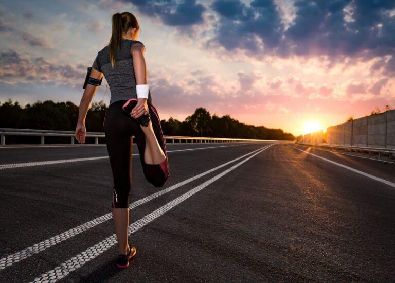 Mulher alongando a perna antes de correr