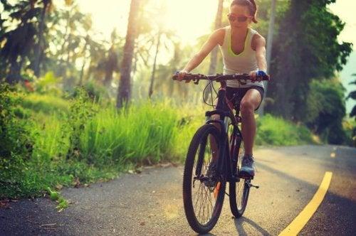 Mulher andando de bicicleta na estrada.