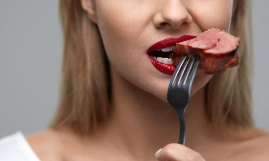 Mulher comendo carne