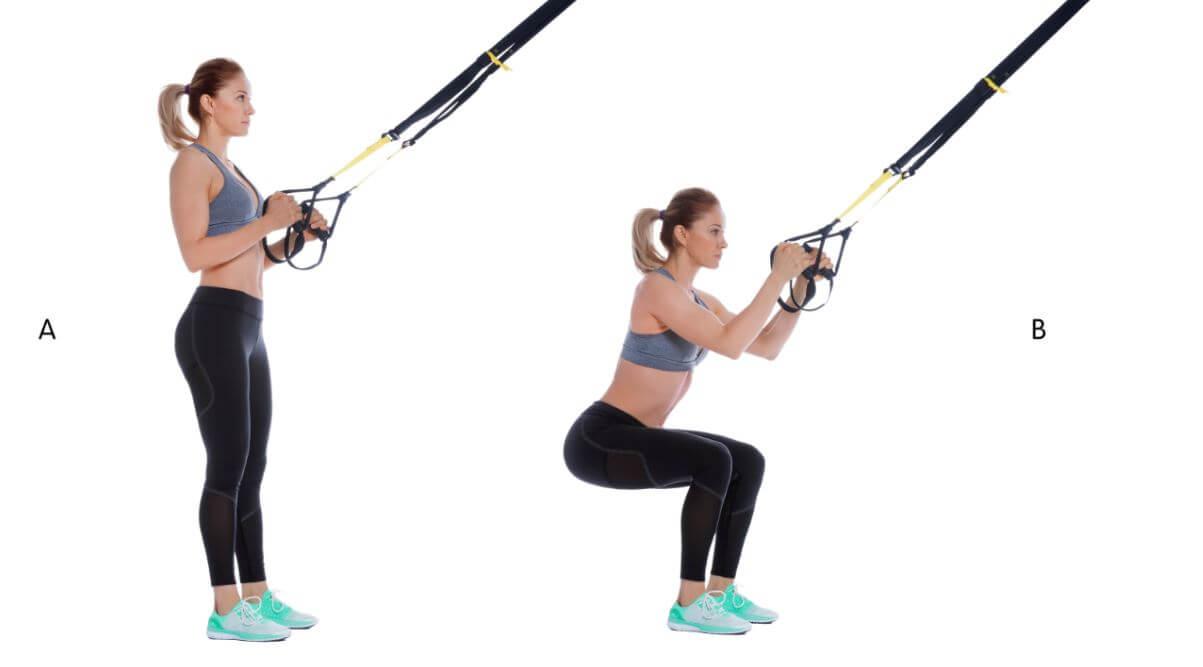 Mulher fazendo agachamentos com corda TRX