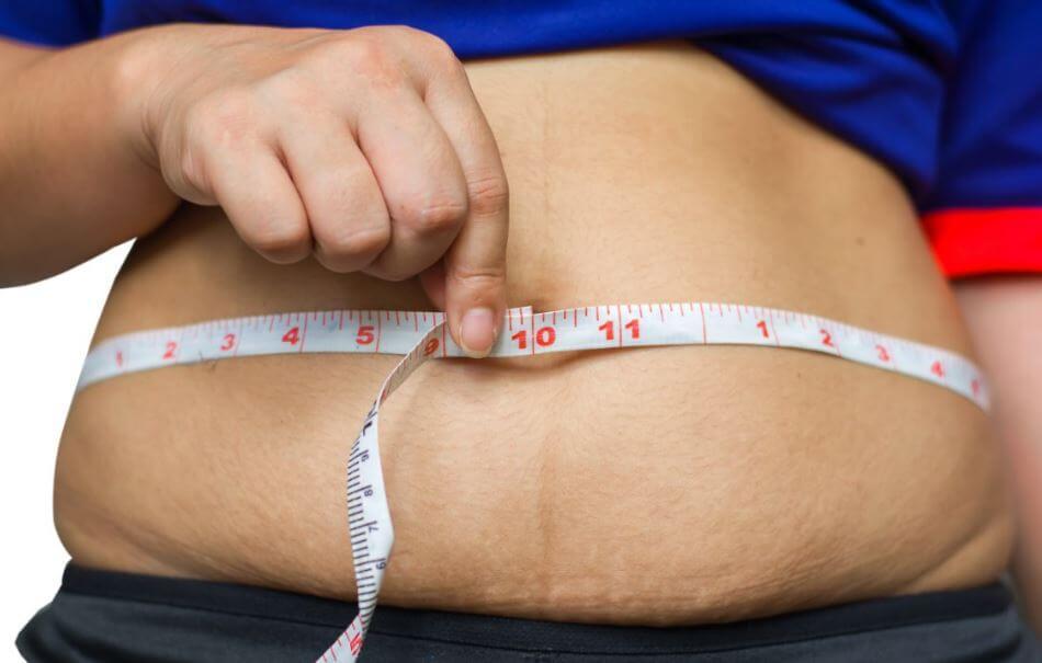 Pessoa medindo a barriga com uma fita métrica