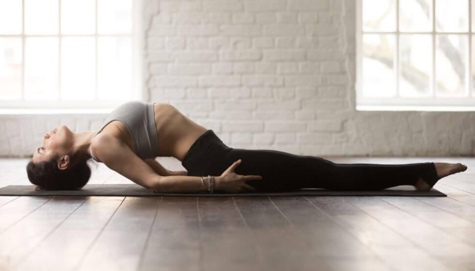Mulher fazendo postura de yoga para as costas