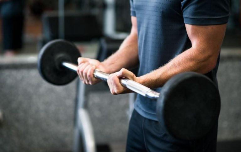 Homem fazendo bíceps com barra