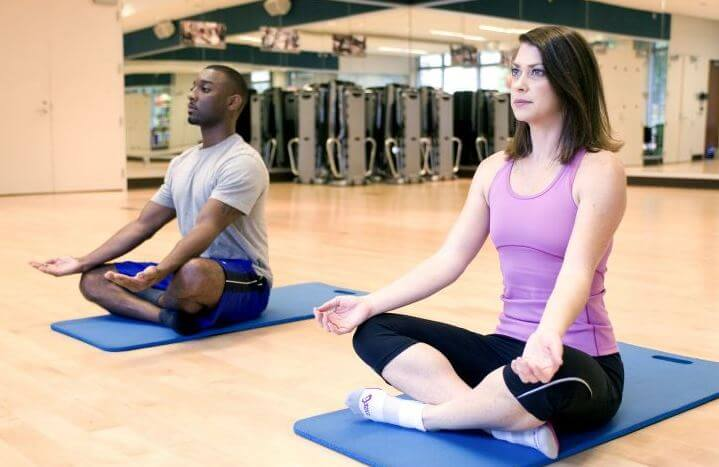 Mulher e homem respirando em postura de yoga