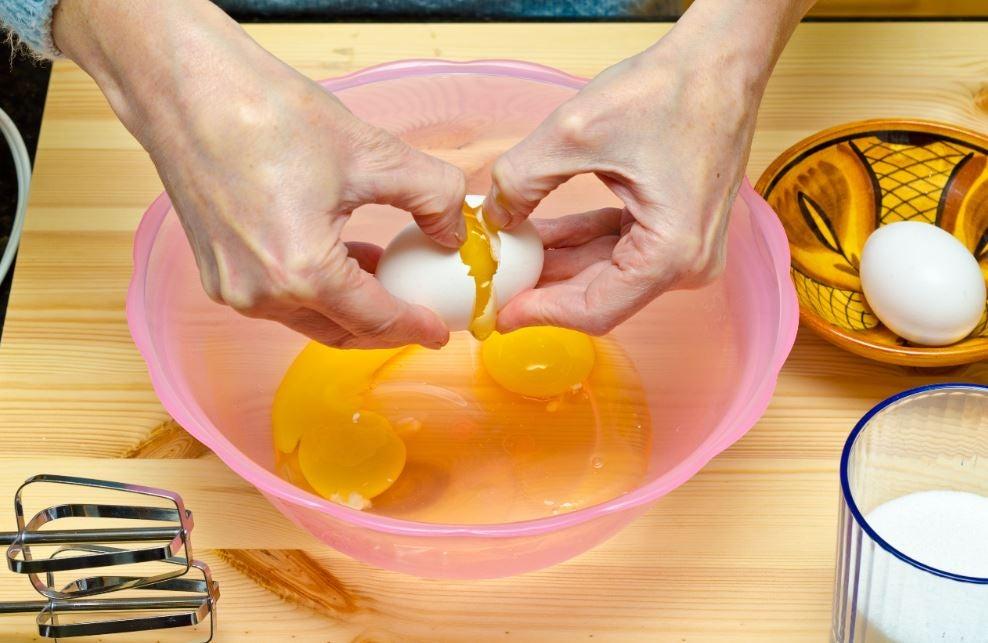 Homem quebrando ovos em uma tigela