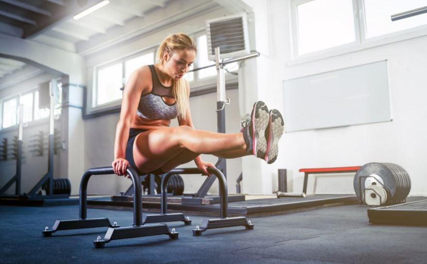 Mulher fazendo abdominais nas barras paralelas