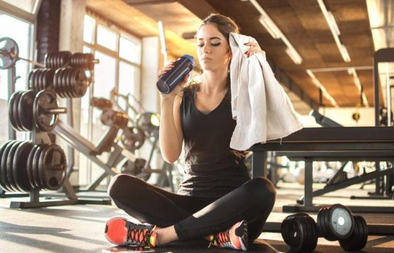 Garota sentada tomando água na academia