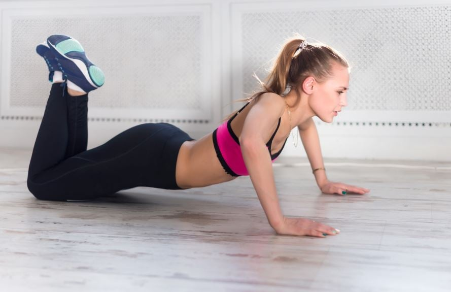 Mulher fazendo flexões no chão