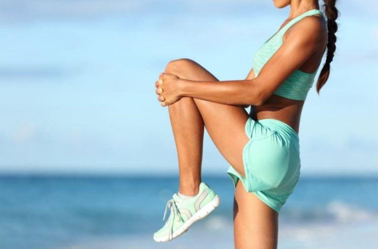 Mulher alongando as pernas para correr na praia