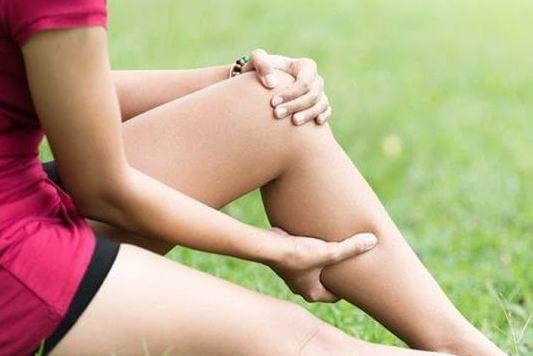 Mulher com câimbra na perna