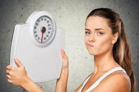 Mulher insatisfeita segurando uma balança