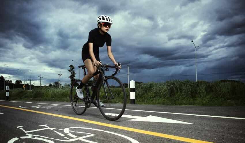 Mulher praticando ciclismo na estrada