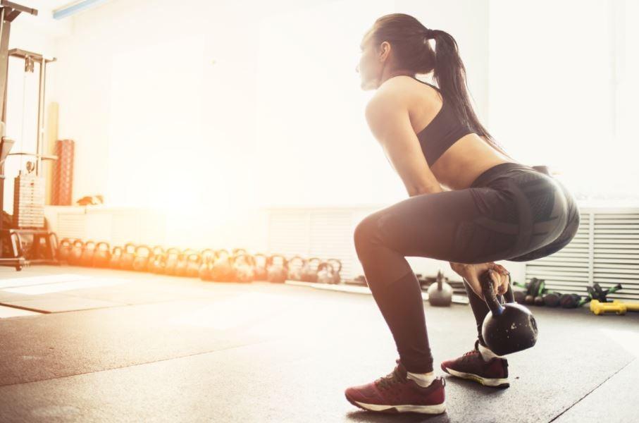 Mulher treinando com peso kettlebell