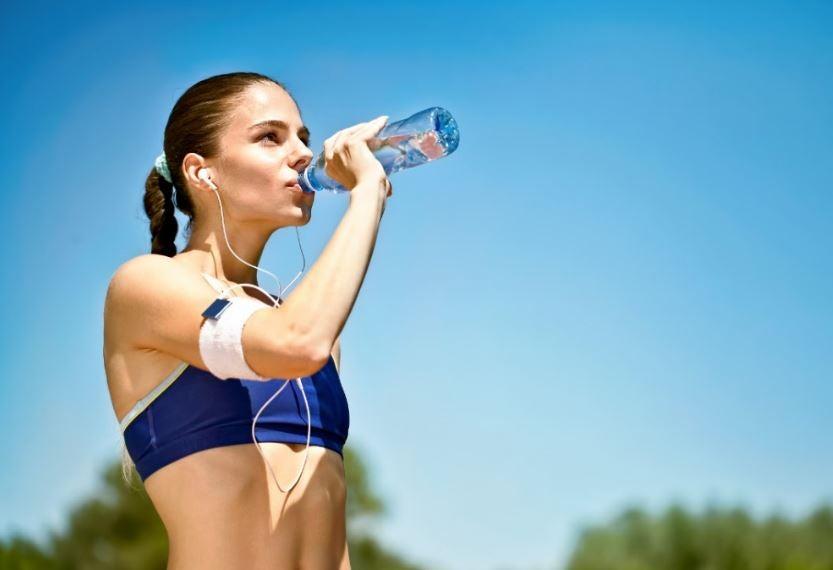 Mulher bebendo água após exercício