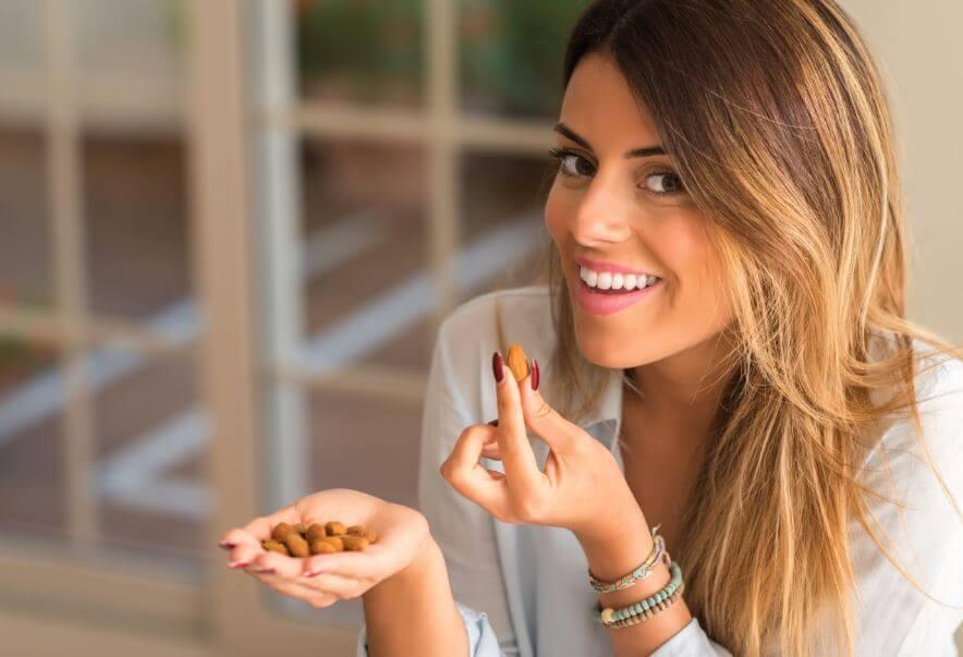 Mulher comendo amêndoas