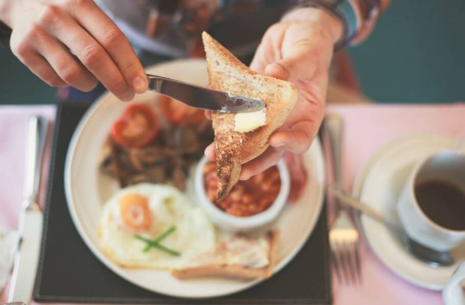 Homem comendo café da manhã com torrada