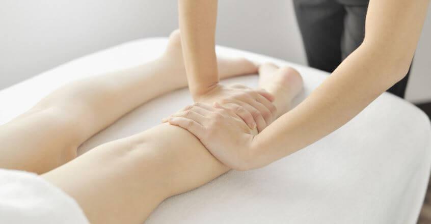 Uma mulher massageando as pernas de outra